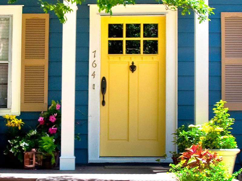 Blue house exterior with yellow door, new windows, flowers, plants, and covered porch area.