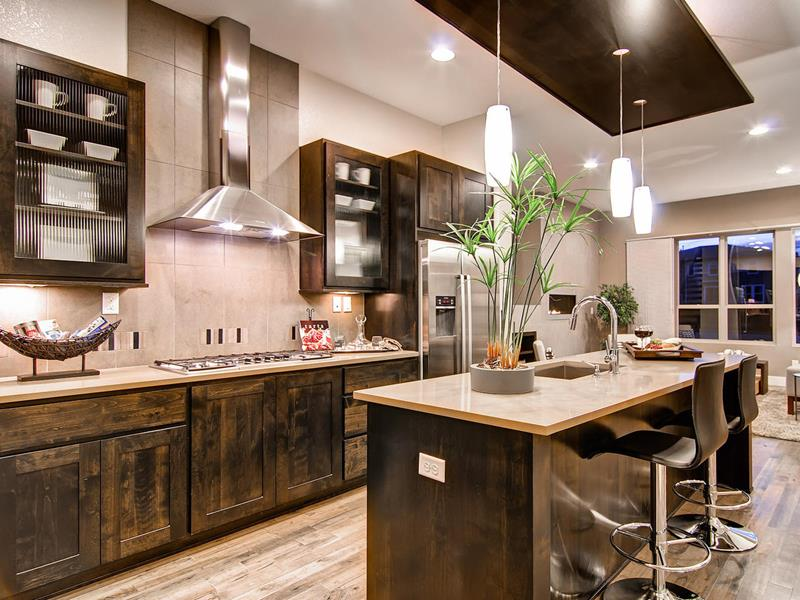 Wide view of rustic kitchen cabinets, large hood and range over a tiled backsplash, glass door cabinets, kitchen island with sink area under new pendant lights, and hardwood floor.